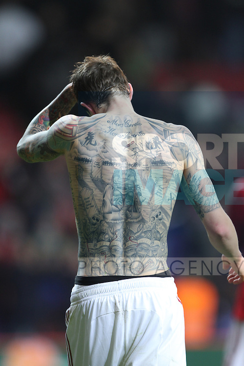 Danish international footballer Daniel Agger exposes his body tattoos after the match against England