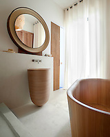 This bathroom combines a wooden basin and bath tub with tinted concrete flooring and walls and is decorated with a 1960s circular mirror