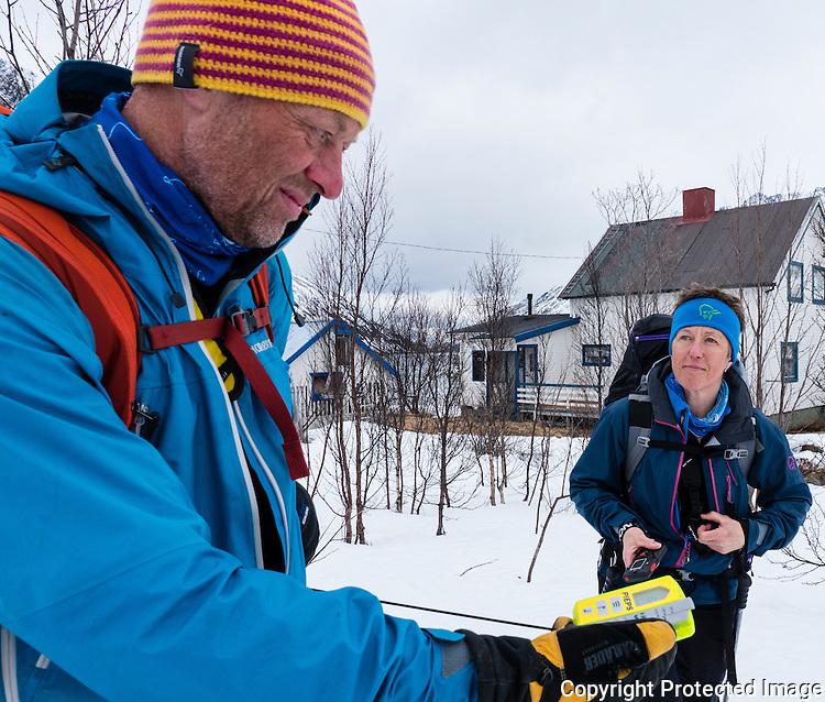 Dame og mann sjekker funksjonen på skredsøker. ---- Woman and man checking beacon.