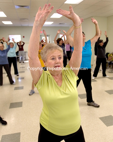 SOUTHBURY CT. 01 December 2014-120114SV02-Pat Foster of Southbury stretches during the get healthy aerobics program at the senior center in Southbury Monday. Over 50 people attend the class. <br /> Steven Valenti Republican-American