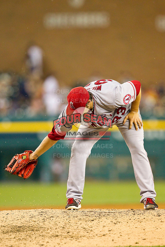 Los Angeles Angels starting pitcher C.J. Wilson (33) cleans off the pitching rubber with his glove during the Major League Baseball game against the Detroit Tigers at Comerica Park on June 25, 2013 in Detroit, Michigan.  The Angels defeated the Tigers 14-8.  (Brian Westerholt/Four Seam Images)