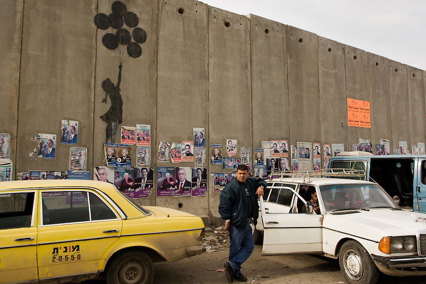 Palestinian taxi drivers wait to drive passengers into the Occupied West Bank by the Israeli 'security barrier' at the Qalandiya checkpoint near Jerusalem, Israel/Palestine, 2006. Photo: Ed Giles.