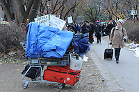 November 21, 2011, an unidentified woman passes by a shopping cart loaded with the belongings of a protester vacating St. James Park following the decision handed down this morning's by Ontario Superior Court judge David Brown, upholding the Occupy Toronto tent camp eviction.