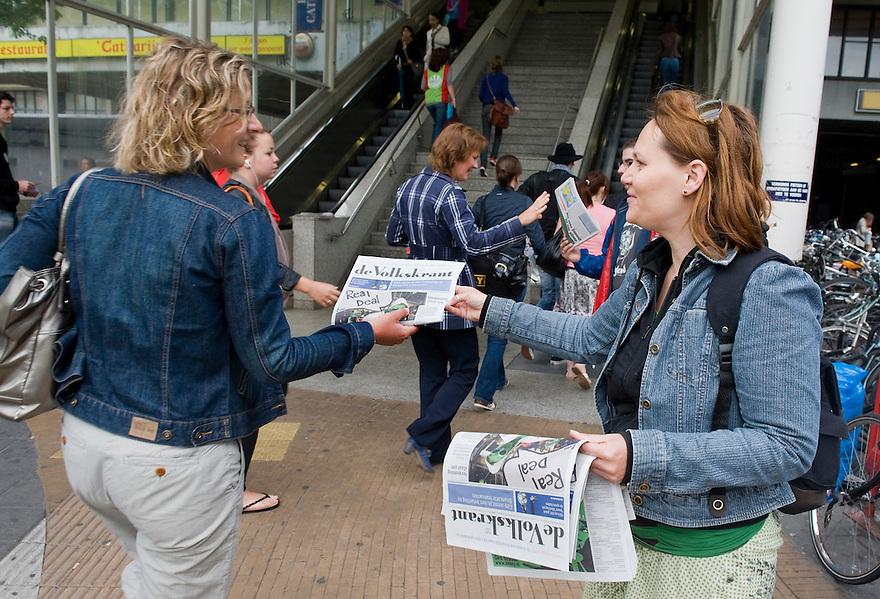 Nederland, Utrecht, 6 juni 2010.Vanmorgen werd in het hele land een spoof van de Volkskrant uitgedeeld. Een 'spoof' is een krant die lijkt op een echte krant, maar bijvoorbeeld door een organisatie gemaakt die zo haar ideeen kwijt kan bij een groot publiek. Bovendien levert het publiciteit op..Foto: uitdelen spoof bij Utrecht Centraal..Foto (c)  Michiel Wijnbergh