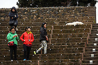Pictured: A stray dog looks unfazed by the female Asian tourists as it sleeps on the upper tier of an ancient theatre in Pompeii, in southern Italy. Thursday 27 February 2014