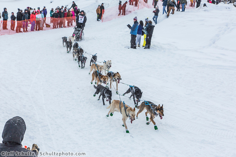 Justin Savidis from Willow, Alaska drops down onto the Chena River with his team shortly after the start of the 2015 Iditarod sled dog race. in Fairbanks. Photo by Todd Paris/IditarodPhotos.com 2015