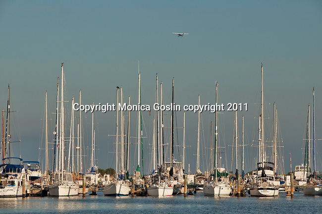 Sunset on the boats at the City Marina in St. Petersburgh, Florida at Tampa Bay with a small plane flying overhead