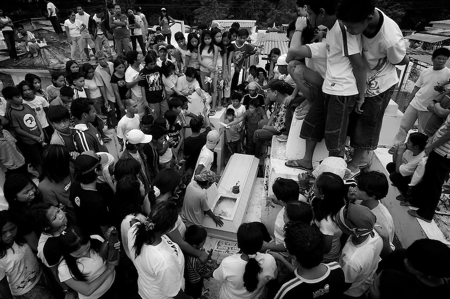 Mourners gather for the funeral of Recto Lumakang, 25, in a cemetery in the Mindanao city of Davao. Lumakang - a young gang member - was killed by a gunshot to the head and several days later the friend who carried him to the hospital was stabbed to death. A death squad - known as the Davao Death Squad or DDS - operates in the city with the tacit support of the city's mayor Rodrigo Duterte killing criminals, gang members, drug users, and occasionally opponents of the mayor and his programs - a situation deplored by human rights groups but quietly accpeted by much of the city's citizenry who benefit from the city's relative stability and security.