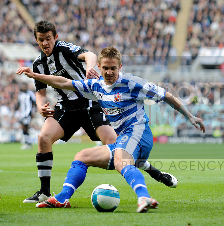 Reading's Kevin Doyle (R) tries to hold off Newcastle's Joey Barton.