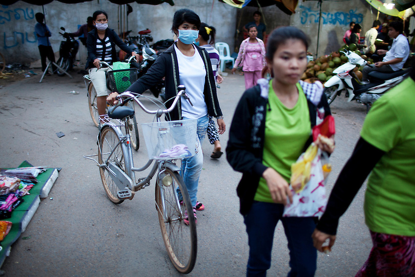 Workers from the Shen Zhou garment factory walk through a small open-air market just after 6 p.m., following the overtime shift, in Phnom Penh, Sept 8, 2011. Standard hours at the factory are 7 a.m. to 4 p.m., with a 1-hour lunch break. Workers receive time and a half for the 2-hour overtime shift, which ends at 6 p.m.