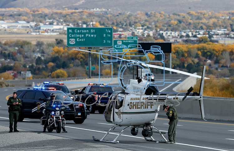 A Washoe County Sheriff's R.A.V.E.N. helicopter clipped power lines above Lakeview Hill and made an emergency landing on I-580, at the north end of Carson City, Nev., on Saturday, Oct. 27, 2018. No one was injured in the incident which also started a small brush fire.<br /> Photo by Cathleen Allison/Nevada Momentum