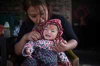 A mother dresses  up her child. Kathmandu, Nepal. May 9, 2015