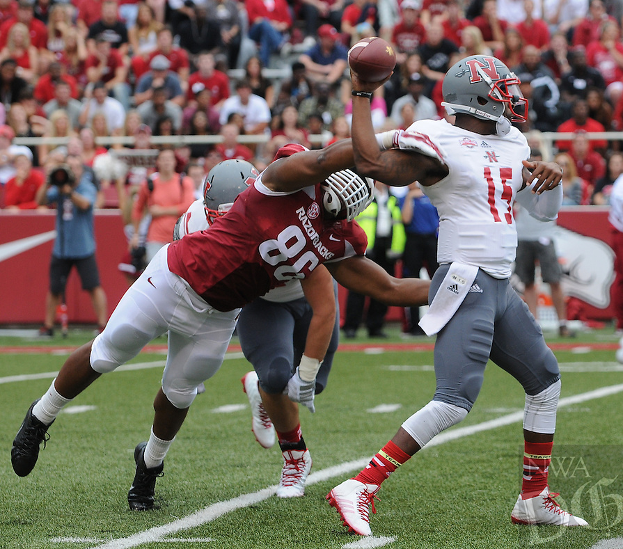 STAFF PHOTO ANTHONY REYES • @NWATONYR<br /> Trey Flowers, Razorbacks defensive end, pressures Kalen Henderson Nicholls State quarterback in the first quarter Saturday, Sept. 6, 2014 at Razorback Stadium in Fayetteville.