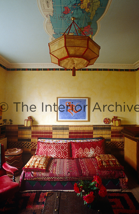 In the living room the sofa is covered in red Moroccan rugs and throws and Moroccan palm fibre matting has been used as a wall-covering halfway up the walls; the framed watercolour is a work by Dhruva Mistry