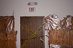 Damaged wall in a building and Do Not corss line accross an exit door