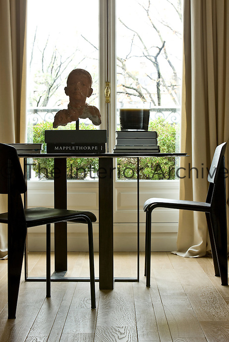 Beside French windows in the living room a contemporary side table displays a collection of books and a bust