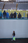 A woman with a shopping bag walks outside the ground as home supporters watch action from the second-half as Greenock Morton (in hoops) take on Stranraer in a Scottish League One match at Cappielow Park, Greenock. The match was between the top two teams in Scotland's third tier, with Morton winning by two goals to nil. The attendance was 1,921, above average for Morton's games during the 2014-15 season so far.
