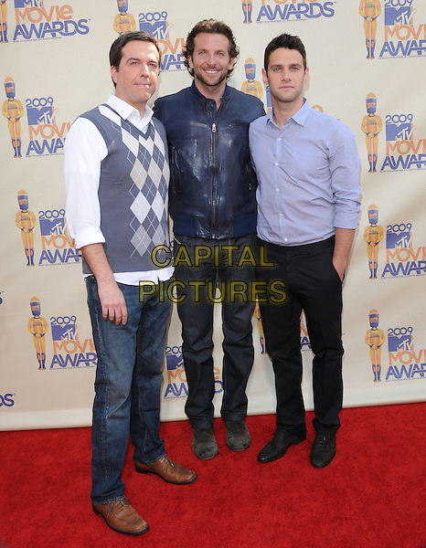 ED HELMS, BRADLEY COOPER & JUSTIN BARTHA.The 2009 MTV Movie Awards held at Universal Ampitheatre  in Universal City, California, USA..May 31st, 2009  .full length blue leather jacket shirt grey gray white argyle pattern vest top arms over shoulders stubble facial hair jeans denim trousers hand in pocket.CAP/DVS.©Debbie VanStory/Capital Pictures.