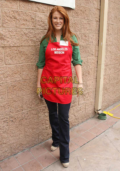 ANGIE EVERHART.Los Angeles Mission Easter For The Homeless Held At The Los Angeles Mission, Los Angeles, California, USA, 22nd April 2011..full length jeans red apron green shirt smiling .CAP/ADM/KB.©Kevan Brooks/AdMedia/Capital Pictures.