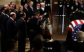 Members of US President Donald Trumps cabinet pay their respects near the casket bearing the remains of former US President George H.W. Bush at the US Capitol during the State Funeral in Washington, DC, December 3, 2018. - The body of the late former President George H.W. Bush travelled from Houston to Washington, where he will lie in state at the US Capitol through Wednesday morning. Bush, who died on November 30, will return to Houston for his funeral on Thursday. (Photo by Brendan SMIALOWSKI / AFP)