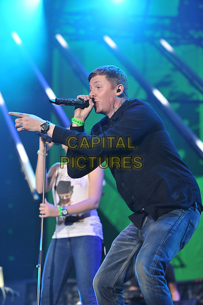 Professor Green - (Stephen Paul Manderson).Orange Rockcorp Concert, Wembley Arena, London, England..July 12th, 2011.stage concert live gig performance music half length black shirt jeans denim side profile singing hand arm pointing lucky scar tattoo.CAP/MAR.© Martin Harris/Capital Pictures.
