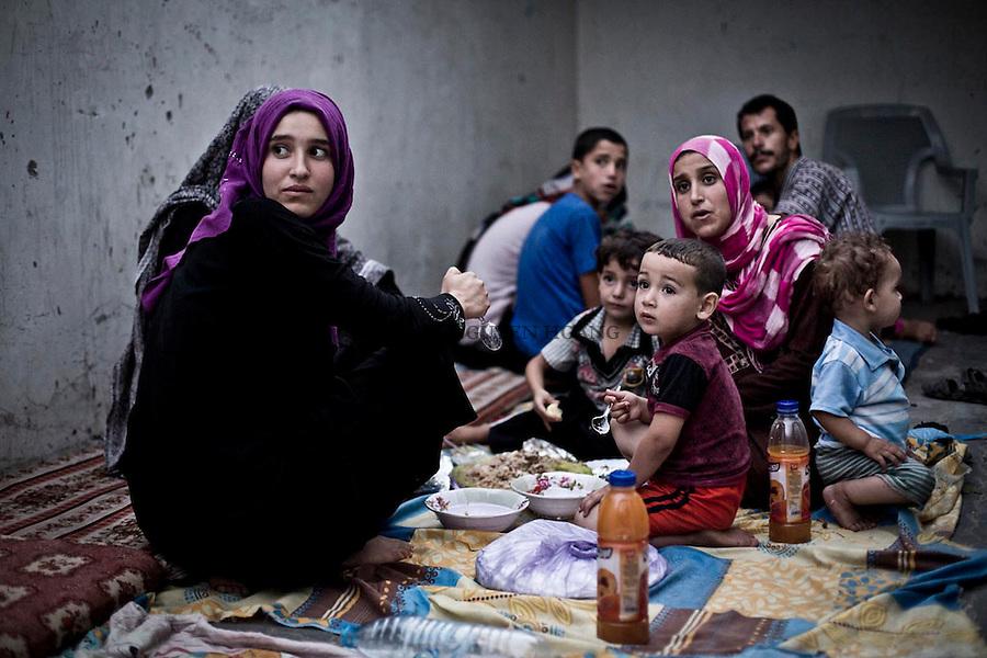 GAZA:  family is eating their iftar in a courtyard of a school. This family has lost its home that was destroyed by shelling in Beit Hanoun, North Gaza. They took refuge in a first school that, a couple of days later, got also hit by a shelling. Now, they've been living in a courtyard of a school in Gaza City.<br /> <br /> GAZA: Une famille mange leur iftar dans la cour d'une &eacute;cole. Cette famille a perdu sa maison qui a &eacute;t&eacute; d&eacute;truite dans les bombardements a Beit Hanoun, au nord de Gaza. Ils se sont r&eacute;fugi&eacute;s dans une premi&egrave;re &eacute;cole qui, quelques jours plus tard, a &eacute;galement &eacute;t&eacute; touch&eacute; par un obus. Ils vivent maintenant dans une cour d'une &eacute;cole de la ville de Gaza.