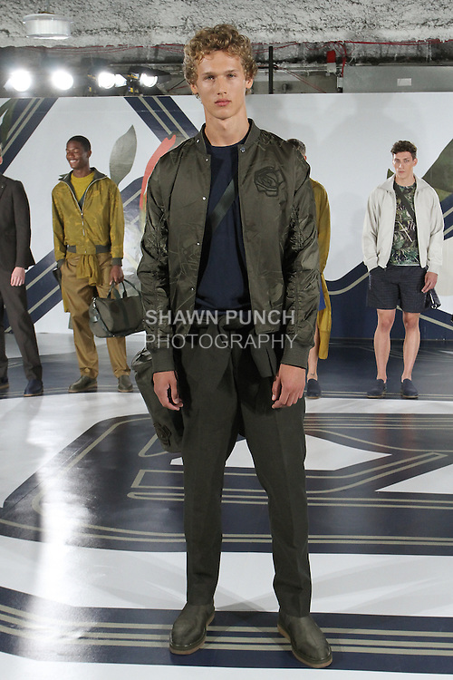 Model Bram poses in a graphic rose jacquard bomber in army, nylon crew neck in navy, and mesh weave suit in army, from the Perry Ellis Spring 2017 collection by Michael Maccari, on July 11th 2017, during New York Fashion Week Men's Spring Summer 2017.