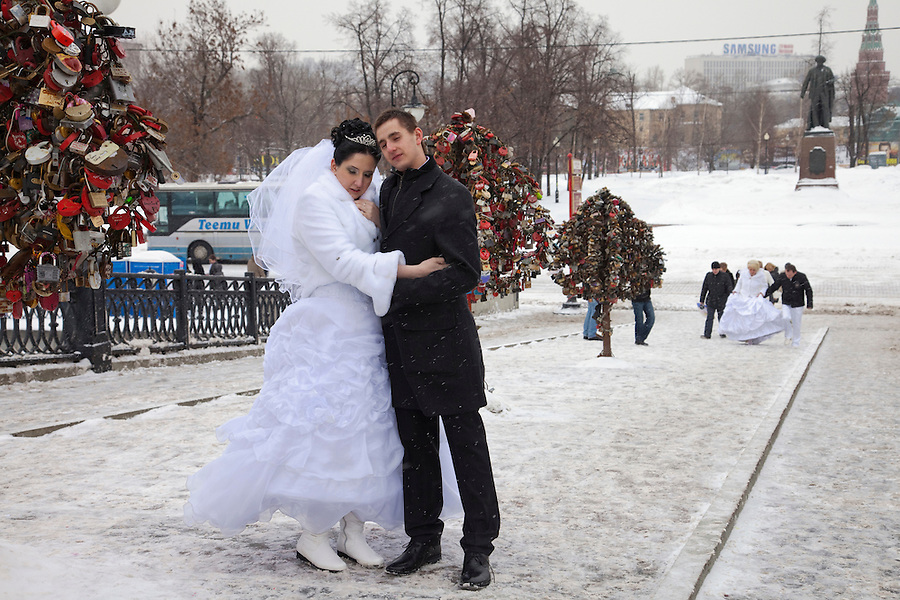 Moscow, Russia, 14/02/2011..Newly-weds visit a city centre bridge in temperatures of minus 14C to hang wedding padlocks on artificial trees.