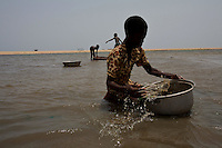Memuna, 11 years old, a young girl catches mussels  in a lagoon in the Volta region, Ghana, on Saturday March 09 2007..