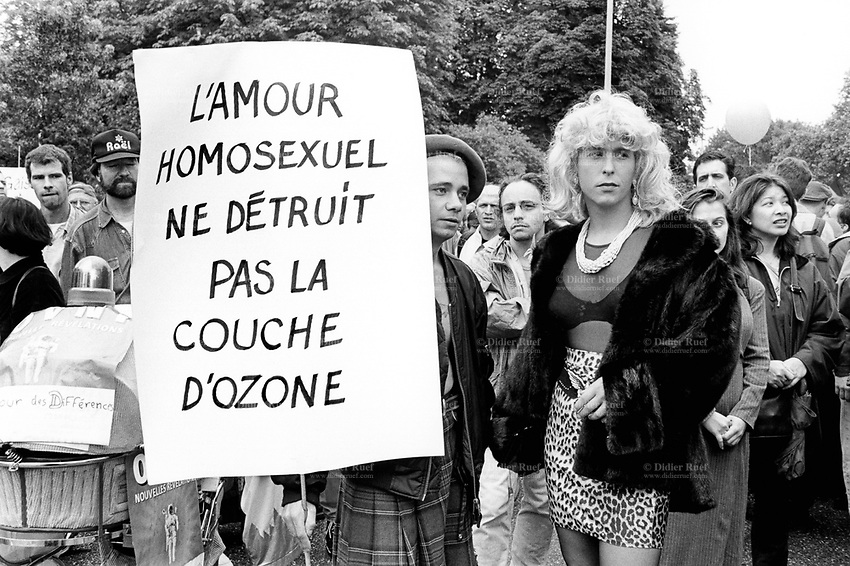 "Switzerland. Geneva. First Gay Pride parade. Two men, both homosexuals, holding a sign which says: "" Homosexual love does not destroy the ozone layer"". © 1997 Didier Ruef"