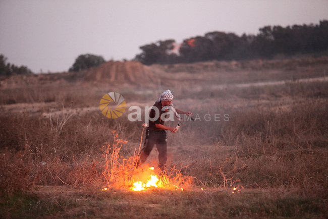 A Palestinian protester tries to throw a molotov cocktail during clashes with Israeli troops near a border fence between Israel and the Gaza Strip on October 14, 2015 east of Bureij in central Gaza. The outbreak of violence between Palestinians and Israeli forces in recent weeks has worsened in October, raising fears of a third intifada, or uprising. Photo by Ashraf Amra