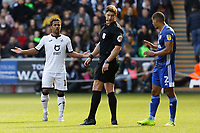Wayne Routledge of Swansea City (L) and Lee Peltier of Cardiff City protest to referee Robert Jones (C) during the Sky Bet Championship match between Swansea City and Cardiff City at the Liberty Stadium, Swansea, Wales, UK. Sunday 27 October 2019