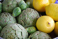 Artichokes, brussell sprouts and lemons in a basket.