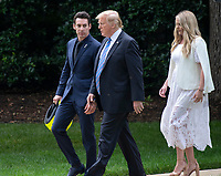 United States President Donald J. Trump, center, walks with winning driver Simon Pagenaud, left, as he greets the 103rd Indianapolis 500 Champions: Team Penske, on the South Lawn of the White House in Washington, DC on Monday, June 10, 2019.  The President took some questions on trade, Mexico, and tariffs against China.  At right is Pagenaud's fiancé Hailey McDermott.<br /> CAP/MPI/RS<br /> ©RS/MPI/Capital Pictures