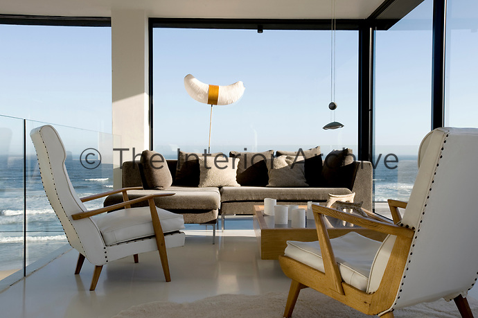 A pair of retro armchairs upholstered in white leather look out onto a view of the ocean through the glass walls of the mezzanine living area