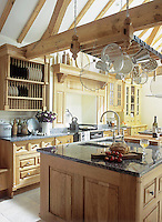 A traditional style kitchen with light wood units. The kitchen has kitchenware hanging from butcher's hooks above a central island unit.