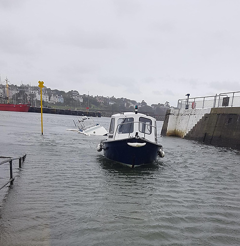 A Bangor Harbour workboat towing the sinking vessel