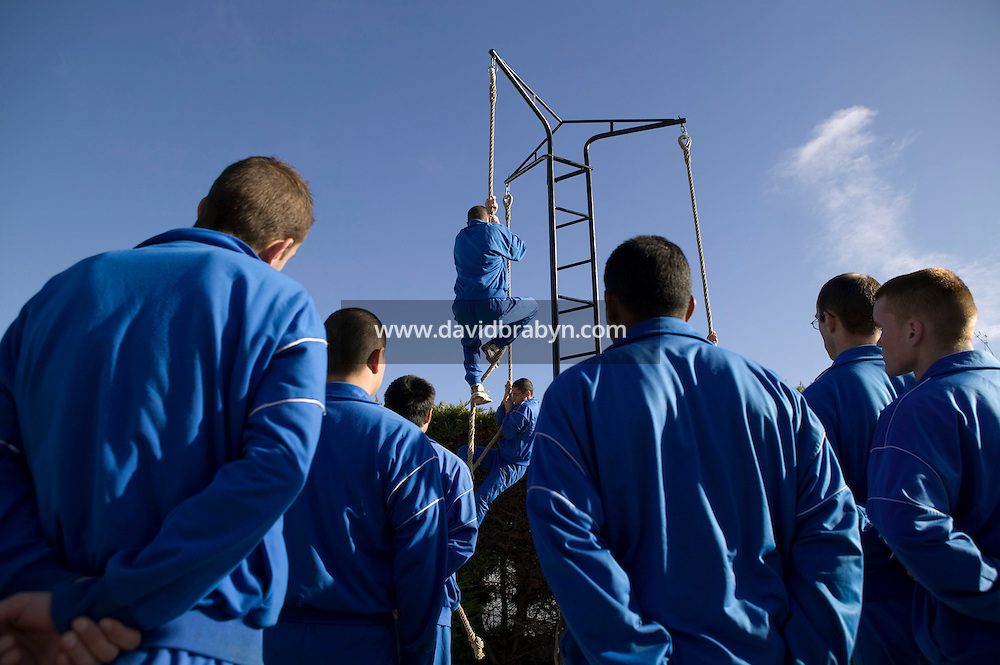 Fresh volunteers to join the French Foreign Legion wearing the traditional light blue suit perform the classic rope climbing exercice at the force's headquarters in Aubagne, France, 10 December 2007.