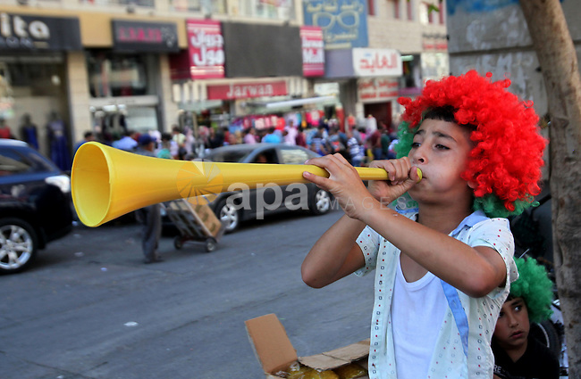 A Palestinian boy celebrates at a street ahead of the Eid al-Adha festival in the West Bank city of Nablus on Sept. 11, 2016. Photo by Nedal Eshtayah