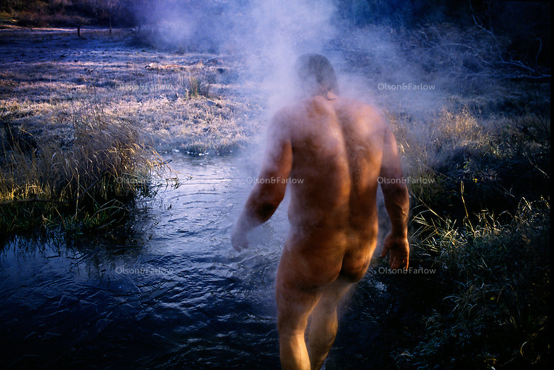 A nude, steaming man enters cold waters outdoors to cool off from a sweat lodge.