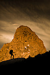 The Grand Teton looms behind a hiker in the high alpine of the Teton Range, Wyoming.