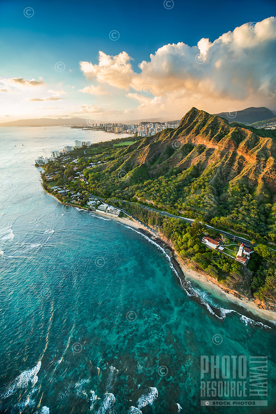 An aerial view of Diamond Head Crater and the southern coast of O'ahu at sunset.
