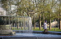 Dog and owner enjoy the cool fountain water in Fairmont Park, Philadelphia, Pennsylvania, PA