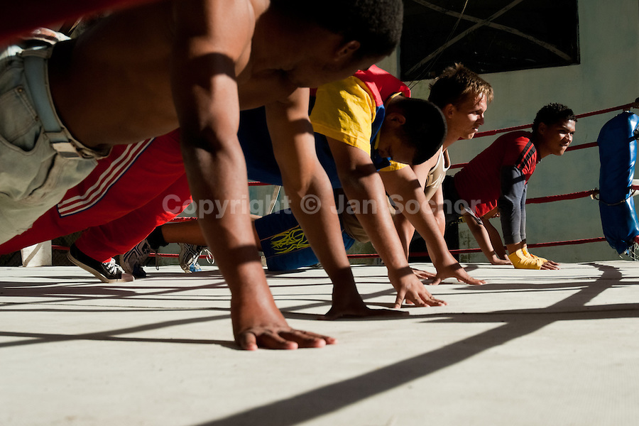 Young Cuban boxers doing push-up exercise during a training drill at Rafael Trejo boxing gym in Havana, Cuba, 5 February 2010. During the last 30 years Cuba has produced more World Champions and Olympic gold medallists in amateur boxing than any other country. Many famous fighters, who came out of Cuba, were training at Rafael Trejo boxing gym in their youth. This run down open air facility in the Old Havana is a place of learning and mastering the art of boxing by the old school style. Boys begin their training very young. As sports are given a high political priority in Cuba, all children are systematically encouraged to develop their skills. Those who succeed will become heroes of Cuban society.