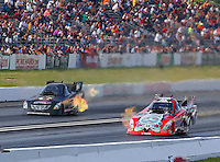 May 31, 2014; Englishtown, NJ, USA; NHRA funny car driver Chad Head (right) races alongside Terry Haddock during qualifying for the Summernationals at Raceway Park. Mandatory Credit: Mark J. Rebilas-