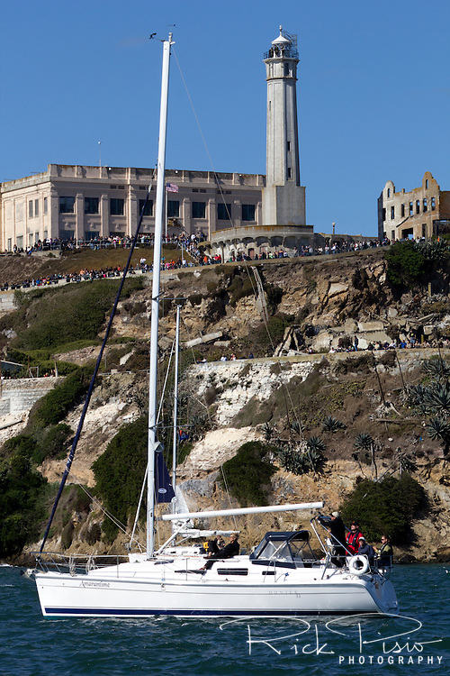 Spectators gather on Alcatraz Island in San Francisco Bay for the Fleet Week Airshow as a sail boat anchors offshore.