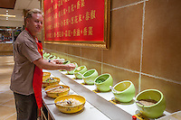 Caucasian male tourist preparing food at a restaurant in Datong, China