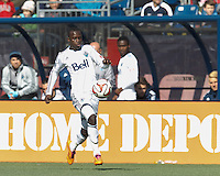 Vancouver Whitecaps FC substitute forward/midfielder Kekuta Manneh (23) dribbles down the wing.  In a Major League Soccer (MLS) match, the New England Revolution (blue/white) tied Vancouver Whitecaps FC (white), 0-0, at Gillette Stadium on March 22, 2014.