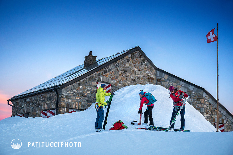 A group of ski tourers putting their skins on at sunrise outside the Tierbergli Hut while on a ski tour of the Berner Haute Route, Switzerland