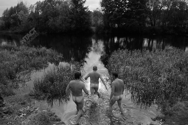 On men's day, a Sunday, at the banya in the large village of Goose Zhelezny in the Ryazan region, after being heated up in the baths, men walked down the banks of the river Goose to cool off in its fast-running water - in the Russian countryside village bathhouses are still a common feature, used by both men and women, and plunging into a river or in winter, snow, a thriving tradition of life in the Russian countryside. Russia, July 20, 2008.